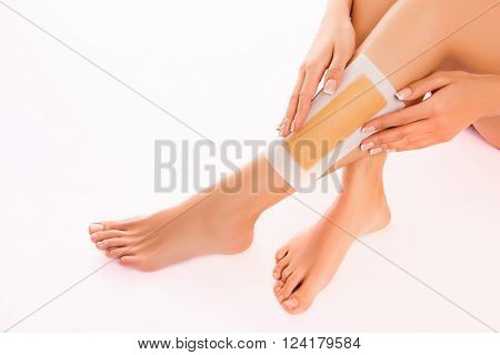 Woman Using Beeswax Stripe To Shave Her Leg, Close Up Photo