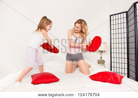 Mother and her daughter playing on bed and fighting with pillows