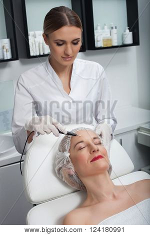 Cheerful beautician is undergoing lather skin therapy for female face. She is standing and looking at human forehead with concentration. The woman is lying and gently smiling