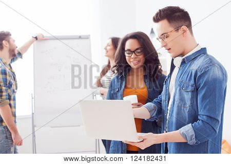 Cheerful young man is explaining to colleague his ideas about project. He is holding a laptop and pointing finger at it. The woman is drinking coffee and smiling. Workers are standing on background