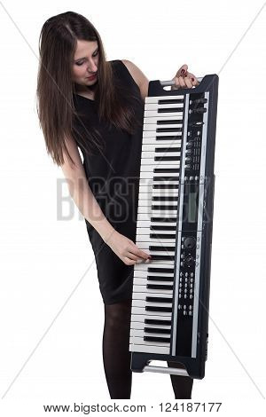 Young woman looking at synthesizer on white background