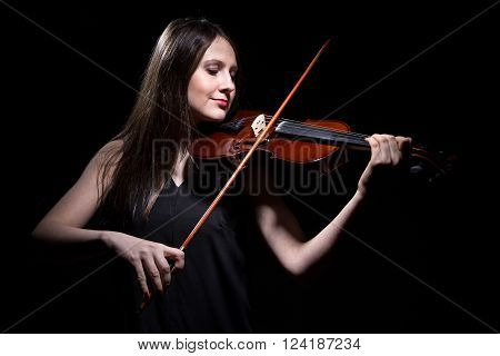 Brunette woman playing on violin on black background