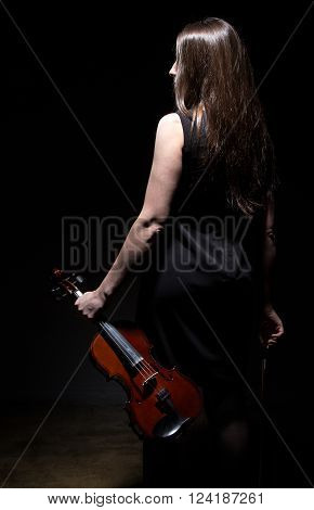 Brunette woman with fiddle from back on black background