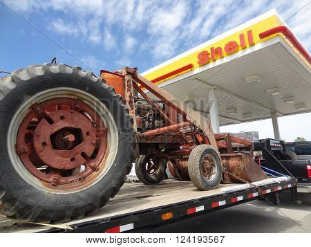 GRAND FORKS, NORTH DAKOTA-June 20, 2013: An old Farmall tractor on a flatbed is parked in front of a Shell gas s, a subsidiary of Royal Dutch Shell.