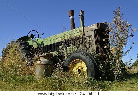 DOWNER, MINNESOTA, October 10, 2015: A n old John Deere  R tractor in the weeds is a product of John Deere Co, an American corporation that manufactures agricultural, construction, forestry machinery, diesel engines, and drivetrains.