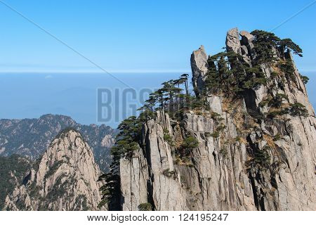 Huang shan the yellow mountain China's most beautiful mountain on a sunny day with deep blue sky and trees and blurry background