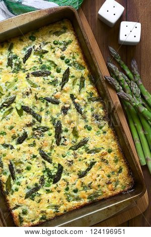 Frittata made of eggs, green asparagus, pea, blue cheese, parsley and brown rice in baking dish, photographed overhead on dark wood with natural light