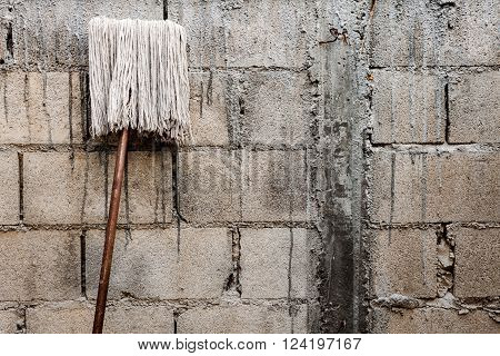 Old mop on wall background . object .