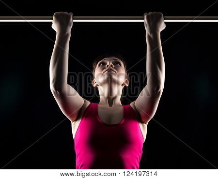 Brunette woman and horizontal bar on black background