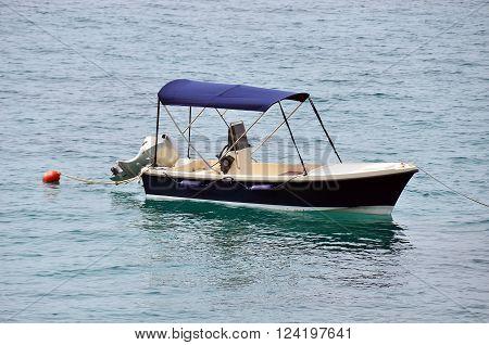 Small blue motor yacht mooring in jetty