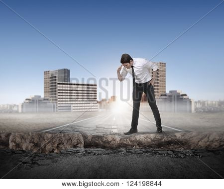 Business Man Looking Down On Broken Road