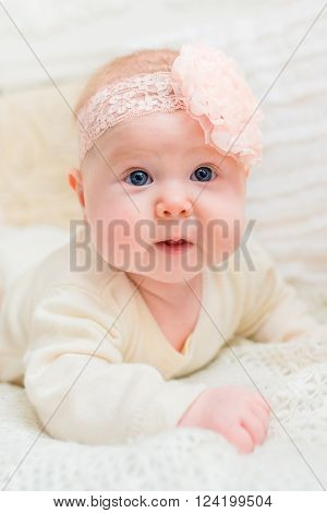 Amazed baby girl with chubby cheeks and big blue eyes wearing white clothes and pink band with flower lying on bed. Babyhood and childhood concept