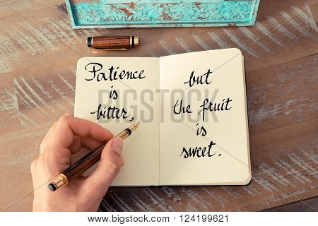 Retro effect and toned image of a woman hand writing on a notebook. Handwritten quote Patience is bitter, but the fruit is sweet as inspirational concept image