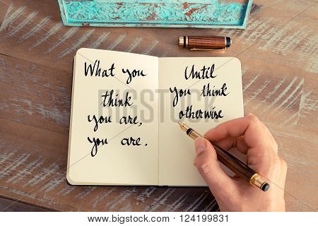 Retro effect and toned image of a woman hand writing on a notebook. Handwritten proverb What you think you are, you are, until you think otherwise as inspirational concept image