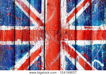 Painted wooden wall or fence with picture of British flag. Natural wooden boards with pattern of Union Jack. Abstract textured background with grunge flag of United Kingdom