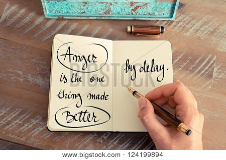 Retro effect and toned image of a woman hand writing on a notebook. Handwritten quote Anger is the one thing made better by delay as inspirational concept image