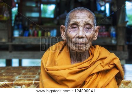 Vang Vieng, Laos - December 13, 2013: Portrait of an old, saffron robed Buddhist monk in Vang Vieng, Laos.