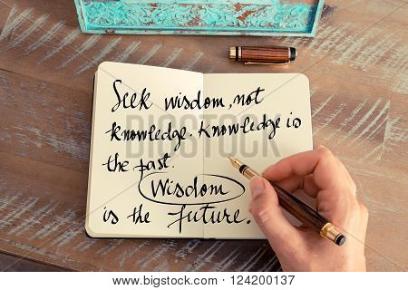 Retro effect and toned image of a woman hand writing on a notebook. Handwritten quote Seek wisdom, not knowledge. Knowledge is of the past, Wisdom is of the future as inspirational concept image