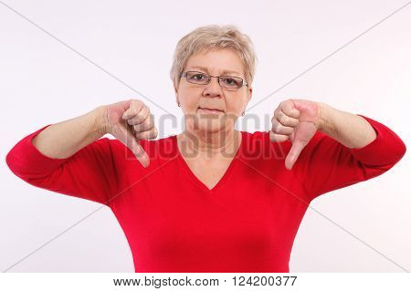 Unhappy and worry elderly senior woman showing thumbs down, disapproval of offer or situation, showing negative human emotions, facial expressions