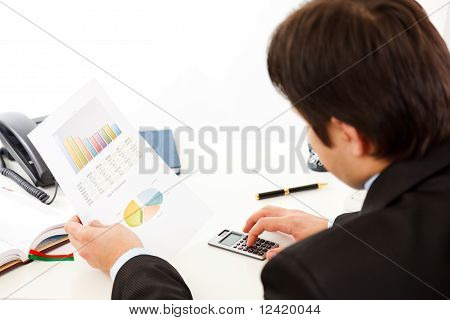 Business man sitting at office desk and checking financial report