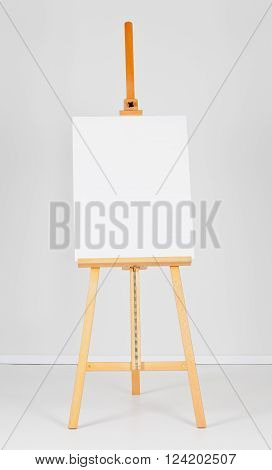 Wooden easel with blank canvas in front of white wall