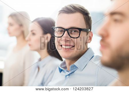 Stay positive. Selective focus of content handsome delighted office worker  smiling and being involved in work while sitting with his colleagues