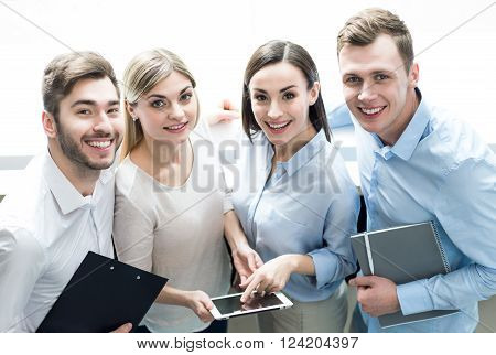 Only together.  Cheerful delighted professional office workers standing and smiling while bonding to each other