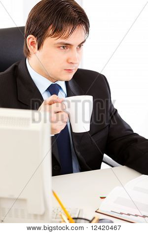 Thoughtful business man sitting at office desk and holding cup of tea in hand
