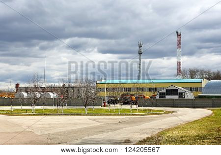 Large industrial facilities with the stock of the construction equipment and trucks nearby