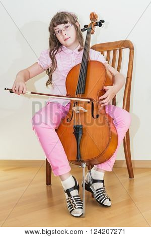 Pretty young girl practice playing cello sitting on chair