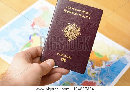 Passport in hand with a world's maps in background