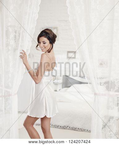 Sexy bride standing in white bedroom in silk slip, smiling.