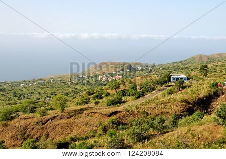 Road descends by a blue house in route to the growing town of Ponta Verde on the Island of Fogo, Cabo Verde