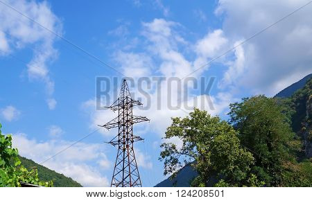 Power transmission tower in the mountains on the background of nature and the sky with clouds.