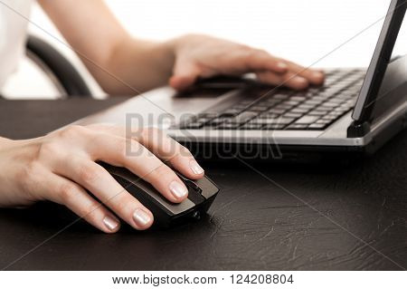 female hands a close up on a mouse and the keyboard of the laptop