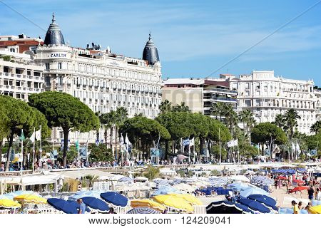 Cannes, France - September 18, 2013: Landscape view of the crowded beach in front of the Carlton International Hotel situated on the croisette boulevard in Cannes, France