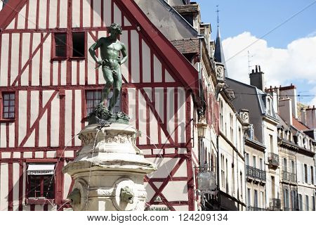 View of the historic city square in Dijon Burgundy France with typical half-timbered houses fountain and statue.
