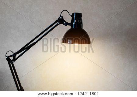 Vintage black reading table lamp turn on in room.