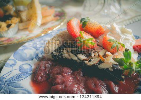 Sponge cake with fresh strawberries and vanilla cream serve with strawberry sauce