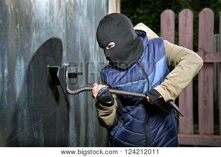 a teen-burglar breaking open of a padlock metal door