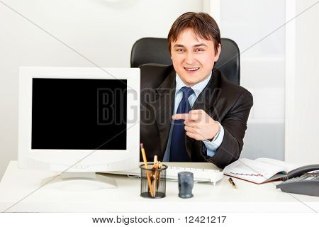 Smiling business man sitting at office desk and pointing finger at monitor with blank screen