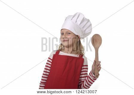 6 or 7 years old little girl in cooking hat and red apron playing cook smiling happy holding spoon isolated on white background looking excited