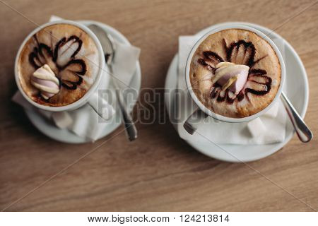 Coffee beautifully decorated with a pattern. cup of latte coffee drinks decorated with latte art and pastry at cafe.