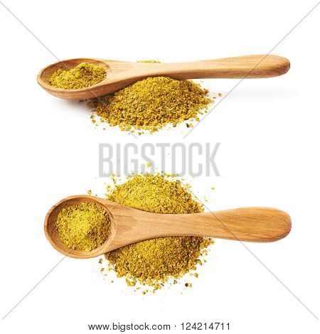 Pile of powdered yellow curry seasoning and wooden measuring spoon over it, composition isolated over the white background, set collection of two different foreshortenings
