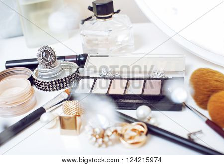 Jewelry table with lot of girl stuff on it, little mess in cosmetic brushes, interior care concept