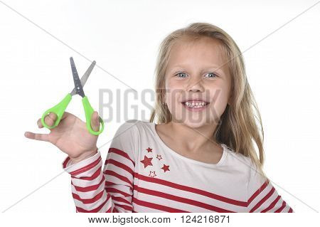 sweet beautiful female child 6 to 8 years old with cute blonde hair and blue eyes holding cutting scissors isolated on white background in education and primary or junior school supplies concept