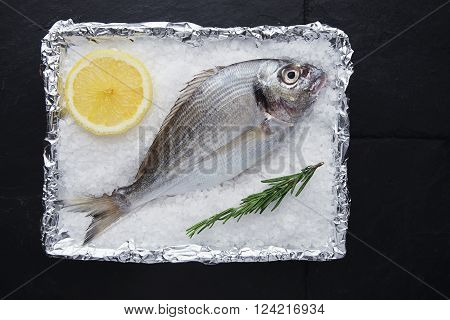 Presentation Of Fresh Wild Sea Bream In Foil Metallic Paper Filled With Stone Salt Grains With Lemon