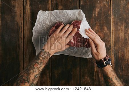 Brutal Man With Tattooed Hands Folds Three Fresh Raw Meat Steaks In White Craft Paper On Vintage Age