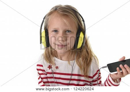 sweet little girl 7 years old with blonde hair and blue eyes listening to music with headphones and mobile phone giving enjoying song happy isolated on white background