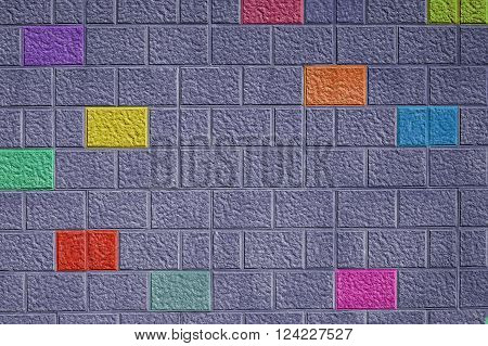Painted gray brick wall background with different colored bricks abstract pattern colorful fun design.